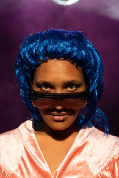 Portraitfoto von Aicha Konaté mit blauer Perücke und sehr großer Sonnenbrille